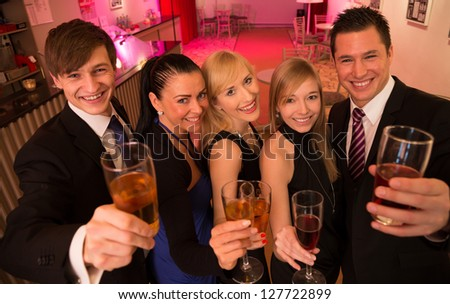 A group of five friends celebrating in a bar and posing for the camera
