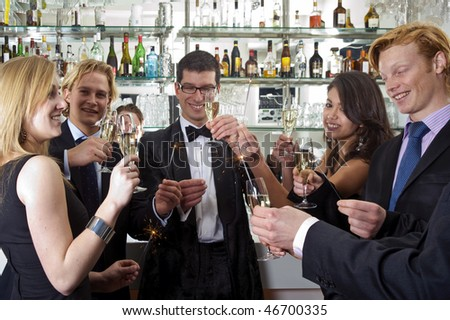 A group of five people celebrating new year at the bar in a club - stock photo