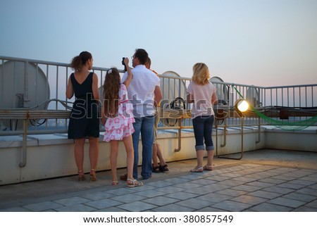 A group of five people with binoculars on the roof of a multistory building against the sky, view from the back - stock photo