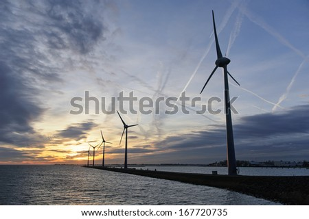 A group of five wind turbines at sunset