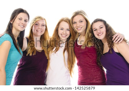 A group of five young teenager girls in casual wear smile at camera.