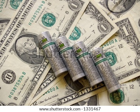 A group of four AA batteries against a background of US currency or money in the form of dollar bills.