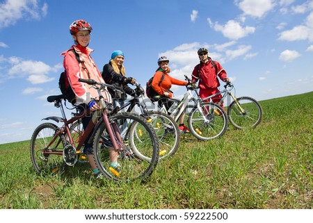 A group of four adults on bicycles in the countryside. - stock photo