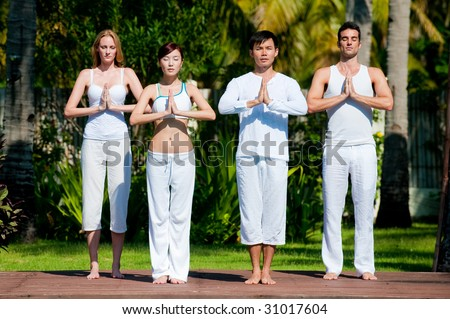 A group of four adults standing outside doing yoga - stock photo