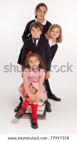 A group of four children of different ages with school uniforms - stock photo