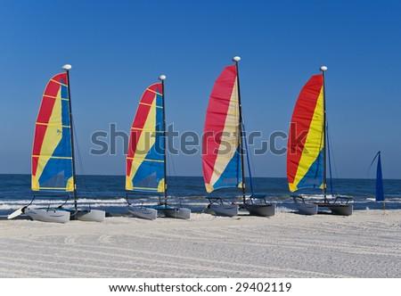 A group of four colorful catamaran sailboats on a tropical beach. - stock photo