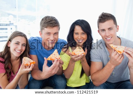 A group of friends about to eat their pizza while they look at the camera - stock photo