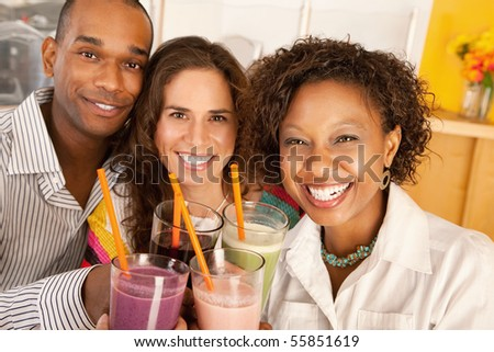 A group of friends are holding smoothies and smiling at the camera.  Horizontal shot.
