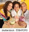 A group of friends are holding smoothies and smiling at the camera.  Square shot. - stock photo