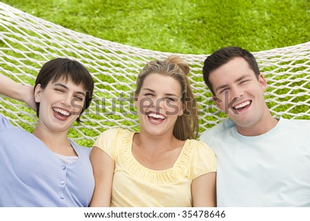 A group of friends are lying together in a hammock and smiling at the camera.  Horizontally framed shot.