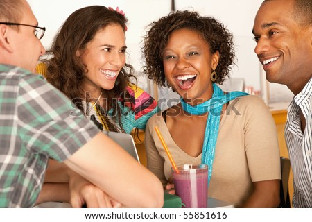 A group of friends are talking and smiling with each other.  One woman is looking towards the camera.  Horizontal shot. - stock photo