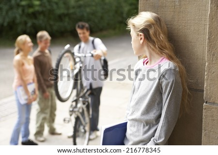 A group of friends chat while a girl looks on. - stock photo