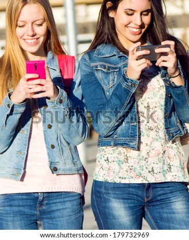 A group of friends chatting with their smartphones in the street