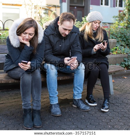A group of friends checking their smartphones while hanging out