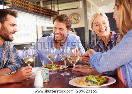 A group of friends eating at a restaurant - stock photo