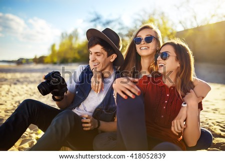 A group of friends enjoying time on the beach. They laugh and smile. Friendly atmosphere. Guys enjoy photos. Well spend the summer. The setting sun - stock photo