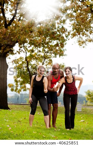A group of friends exercising in the park - giving the thumbs up - stock photo
