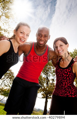 A group of friends exercising in the park on a warm sunny day