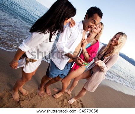 A group of friends having fun at the beach, looking at a cellphone - stock photo