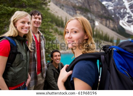 A group of friends hiking with a mountain landscape in the background - stock photo