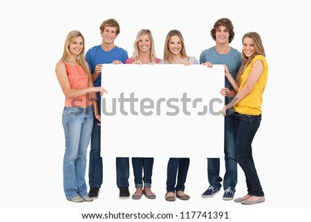 A group of friends holding the blank sheet - stock photo