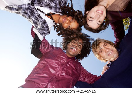 A group of friends hugging and looking down on the camera - stock photo