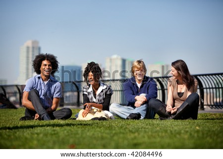 A group of friends in a city park talking and laughing - stock photo
