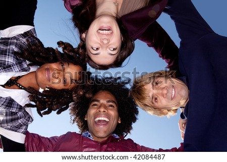 A group of friends in a huddle forming a circle - stock photo