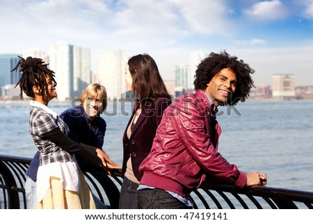 A group of friends in the city - overlooking a harbor and skyline - stock photo