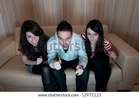 A group of friends intensely watching television - stock photo