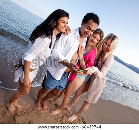 A group of friends laughing at a cellphone, funny text message or picture - stock photo
