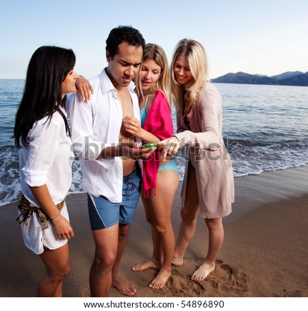 A group of friends looking at a cellphone at the beach - stock photo