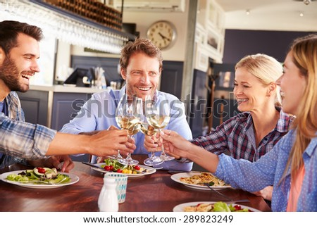 A group of friends making a toast at a restaurant, portrait - stock photo