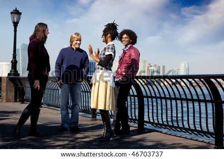 A group of friends on a city walk way by the water - stock photo