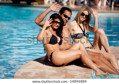 A group of friends on a holiday at a hotel pool waving to the camera