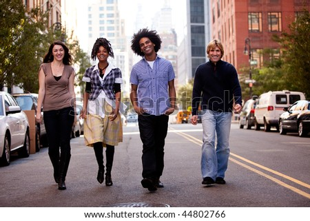 A group of friends on a street in a large city - stock photo