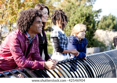 A group of friends outside in a park having fun - shallow depth of field with sharp focus on first person - stock photo