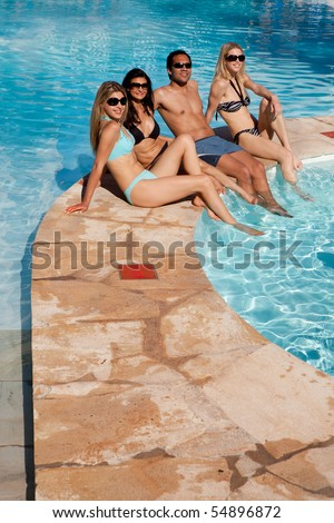 A group of friends relaxing at and outdoor hotel pool