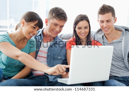 A group of friends smiling as they watch the screen of the laptop with one girl pointing something out - stock photo