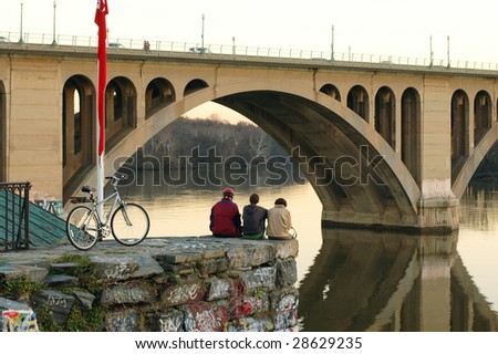 A group of friends take in the beautiful view of the Potomac River and the Key Bridge in Washington DC. - stock photo