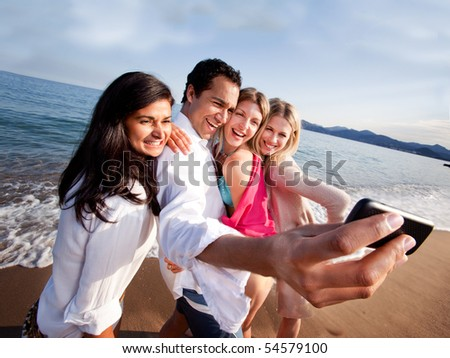 A group of friends taking a self portrait with a camera phone - stock photo