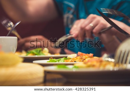 a group of friends to eat pizza, hands, hand with a knife cut on the plate on wooden background