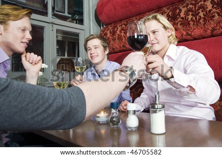 A group of friends toasting their wine glasses in a restaurant. - stock photo
