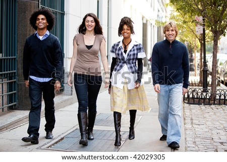 A group of friends walking on the sidewalk in an urban setting - stock photo