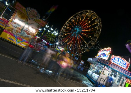A group of friends wanders through a colorful carnival at night