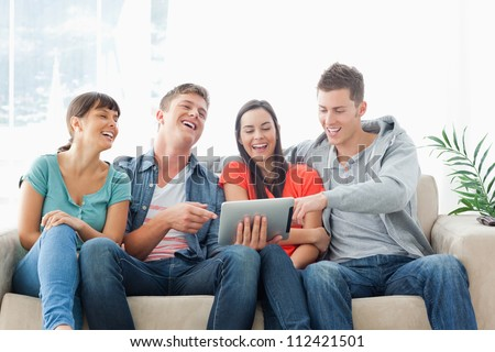 A group of friends watch the tablet pc and laugh as one man points to something on the screen - stock photo