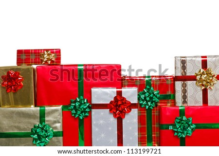 A group of gift wrapped Christmas presents with bows and ribbons, isolated on a white background and positioned lower frame for you to add a message above. - stock photo