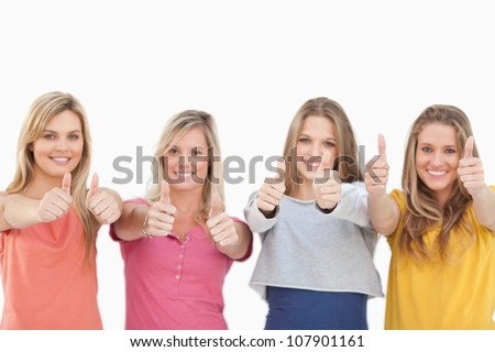 A group of girls looking at the camera while smiling and giving a thumbs up - stock photo