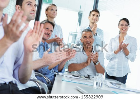 A group of happy business people clapping in a meeting - stock photo