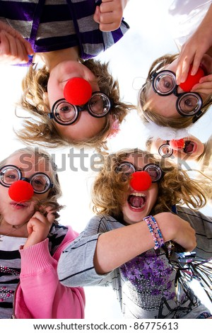 A group of happy children wearing clown noses and silly glasses looking down on the camera. - stock photo